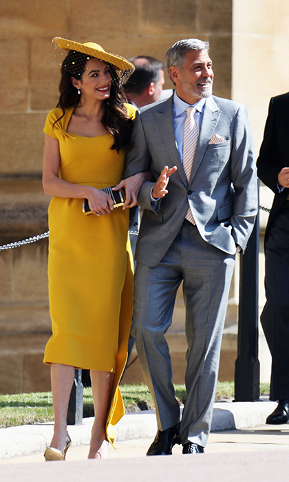 Amal Clooney stole the show in a mustard yellow Stella McCartney ensemble with a matching veiled hat. She arrived with husband George Clooney, who looked dapper as ever in a grey suit with a tie and pocket square that drew from the hues of his wife's ensemble. Meghan and Amal share the same London hairstylist. 