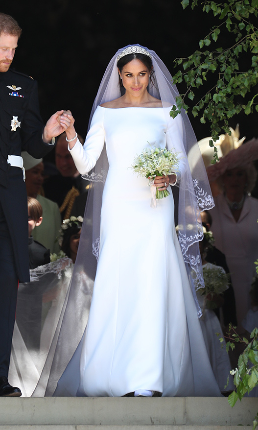 "<p>Meghan's timeless bridal look drew a global gasp of approval! Her classic design by Clare Waight Keller for Givenchy was made with silk fabric, featuring a bateau neckline, three-quarter-length sleeves and fashioned with a long train. Her spectacular 16-foot veil made from silk tulle was embroidered with every flower from the British commonwealth, a meaningful touch that delighted royal watchers. She was solid on her feet thanks to a custom pair of Aquazzura pumps with baby blue soles (a very chic ""something blue"") and wore Cartier's Galanterie de Cartier earrings and Reflection de Cartier bracelet. The piece de resistance? The Queen Mary's diamond bandeau tiara borrowed from the Queen.</p>