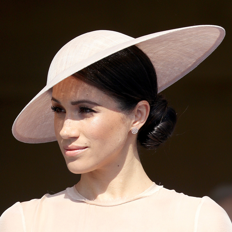 Meghan kept her makeup natural, as she did on her wedding day, rocking a light smoky eye and pretty pink lip. But in a more royal-friendly turn, she traded her messy chignon for a coiffed side bun at the nape of her neck, topping the 'do with an asymmetrical Philip Treacy hat.