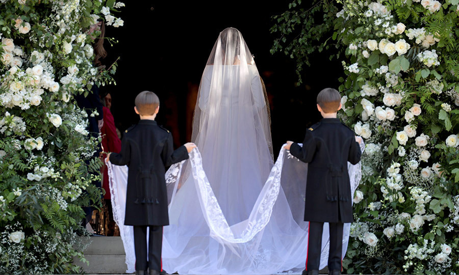 "Photographer Jane Barlow captured this symmetrical moment as twin pageboys Brian and John Mulroney – sons of Meghan's BFF Jessica Mulroney – helped the bride with her hand-embroidered floral Givenchy veil as she entered the church. Jessica later posted a photo from the wedding to Instagram, captioning it: ""Proud friend. Proud mom.""