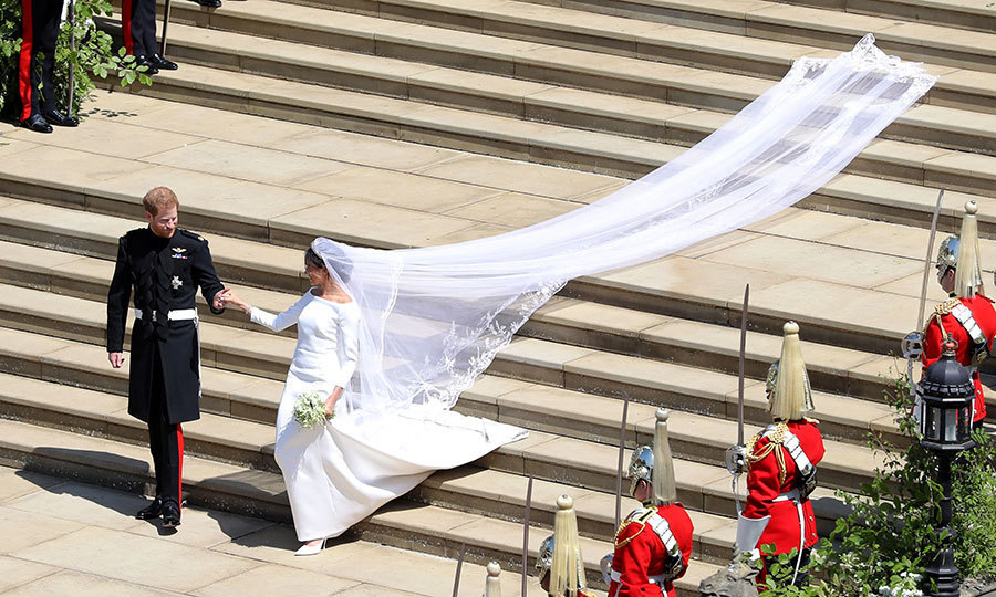 In a photograph evoking the happily ever after of a Disney fairytale, the Prince holds Meghan's hand as the train of her Givenchy gown drapes the stairs in front of St George's Chapel.