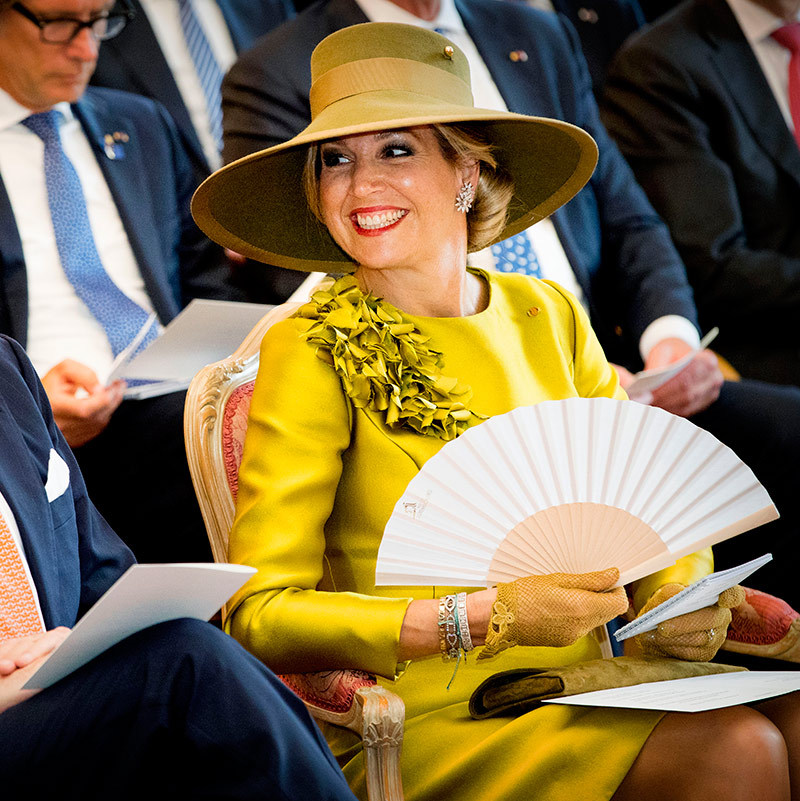 While on a state visit to Luxembourg, the monarch perfectly accessorized her mustard-hued dress with a wide-brimmed hat and a fan to keep the heat at bay. 