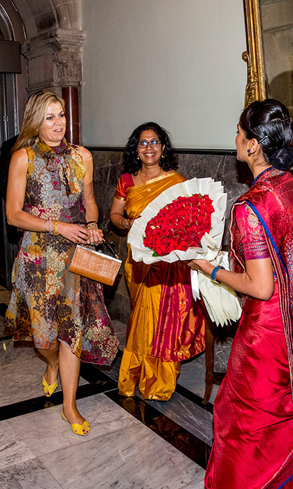 <p>Maxima changed out of her previous outfit into a floral dress, but kept her yellow shoes the same.