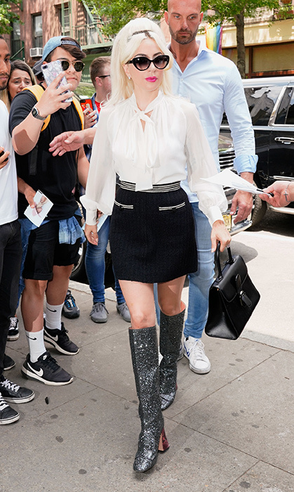 Those boots were <em>definitely</em> made for walking. Gaga paired a flowy white Giambattista Valli top with a Chanel skirt, Rochas boots and Delvaux bag.