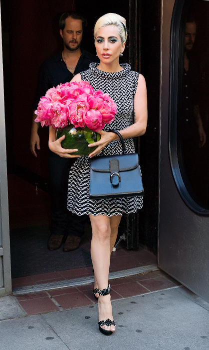 The 32-year-old threw it back to the 70s with this look! Dazzling in an Azzedine Alaïa dress, Gaga clutched a vase of peonies, an elegant Delvaux bag and finished off the look with a swipe of bright blue shadow.