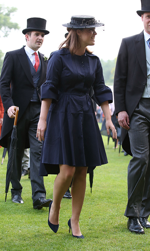 "Though there were 8,000 guests at the Queen's May 2018 garden party, Princess Eugenie still managed to stand out in a chic shirt dress with bell sleeves, matching navy pumps and a Misa Harada hat emblazoned with the word ""Love"" - a fitting symbol for Britain's next royal bride-to-be! 