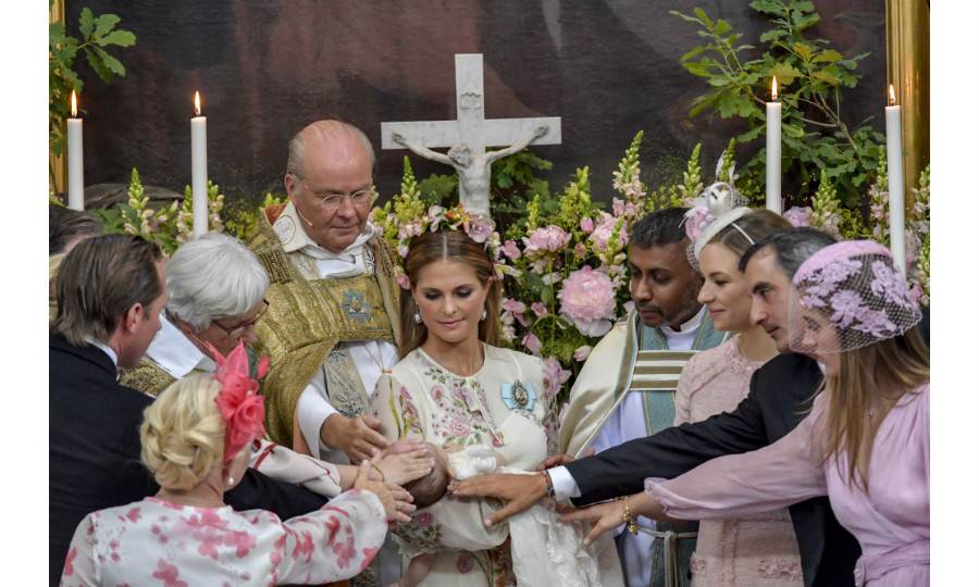 Princess Madeleine holds her daughter as godparents – Anouska d'Abo, Coralie Charriol Paul, Nader Panahpour, Gustav Thott, Charlotte Kreuger Cederlund, Natalie Werner – take part in the christening.