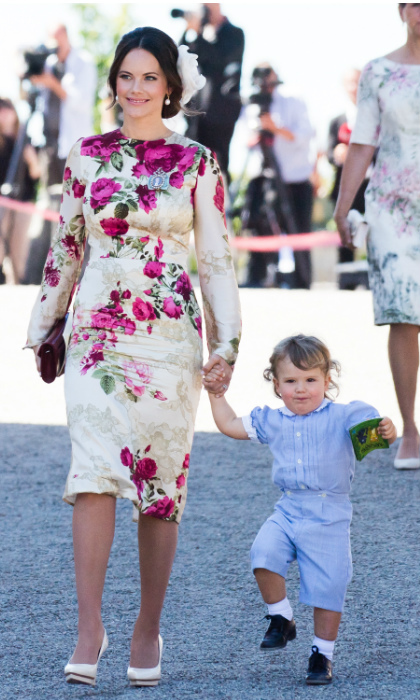 "Princess Sofia dazzles in a pink and cream floral dress as she arrives to the ceremony with her eldest son <a href=""https://ca.hellomagazine.com/tags/0/prince-alexander"" target=""_blank"">Prince Alexander</a>, 2. Here, the adorable toddler skips alongside his mother wearing a blue one-piece from his father's closet. Prince Carl Philip was pictured wearing the garment back in 1982. 