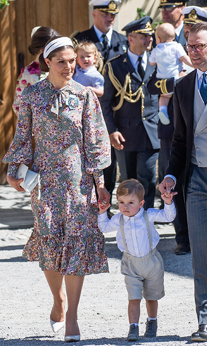 Ever the fashion maven, Crown Princess Victoria attended the christening with Prince Oscar and Prince Daniel, wearing a beautiful grey and pastel floral dress. We especially love her matching white pumps and headband!