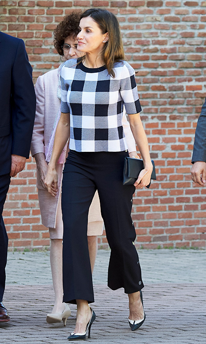 Queen Letizia oozed cool in flared black pants, navy Magrit pumps and a gingham shirt to match. She was wearing nearly head-to-toe Hugo Boss – the 'Floriza' Gingham Wool Blend Knit Top, and pants and High-Waist Wide-Leg Pants. The Spanish royal was visiting a traditional students residence on June 7 in Madrid.