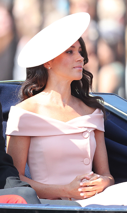 Meghan Markle's second official appearance as a royal was one of the most highly-anticipated royal events of the year – Trooping the Colour, in celebration of the Queen's birthday! The Duchess of Sussex wore a stunning peach pink Carolina Herrera dress, featuring an off-the-shoulder neckline and large button detail. She polished off the look with a gorgeous matching hat, simple jewelry and natural makeup to let her post-honeymoon glow shine through.