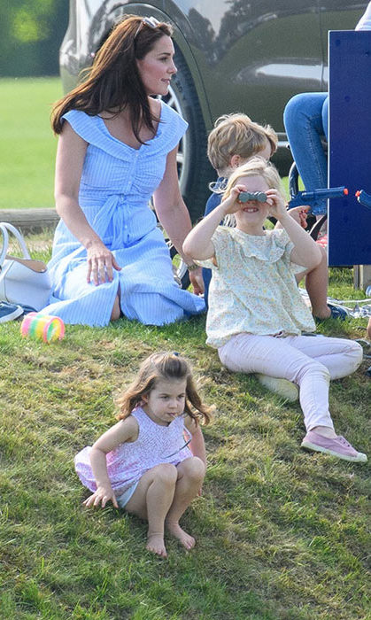 Charlotte kicked off her shoes for the day and scooted down the hill on her bum. She looked adorable in a pink floral dress with her hair half back and a pair of matching pink sunglasses.