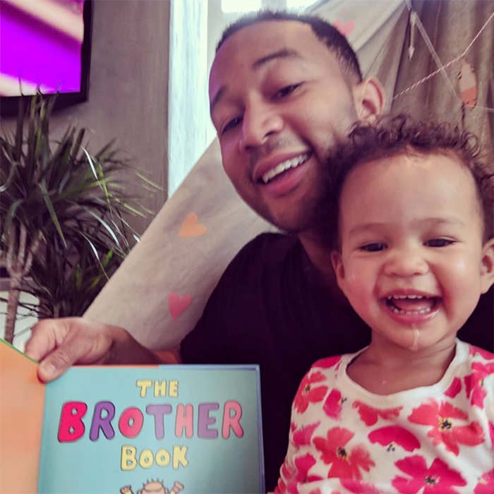 """Prepping for a new arrival!"" John captioned this post of him reading The Brother Book to little Luna. 