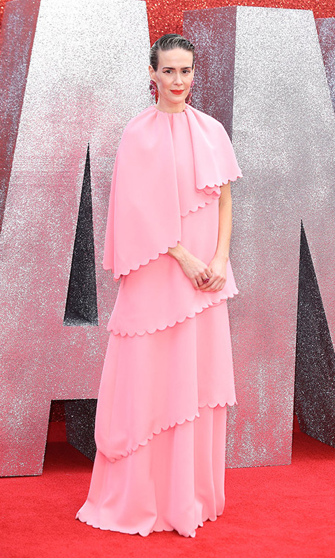 Sarah Paulson brought a dash of whimsy to the event in a pretty pink Valentino gown that featured an asymmetrical cape and scalloped edges. To top it off, she slicked back her hair and wore large pink earrings.