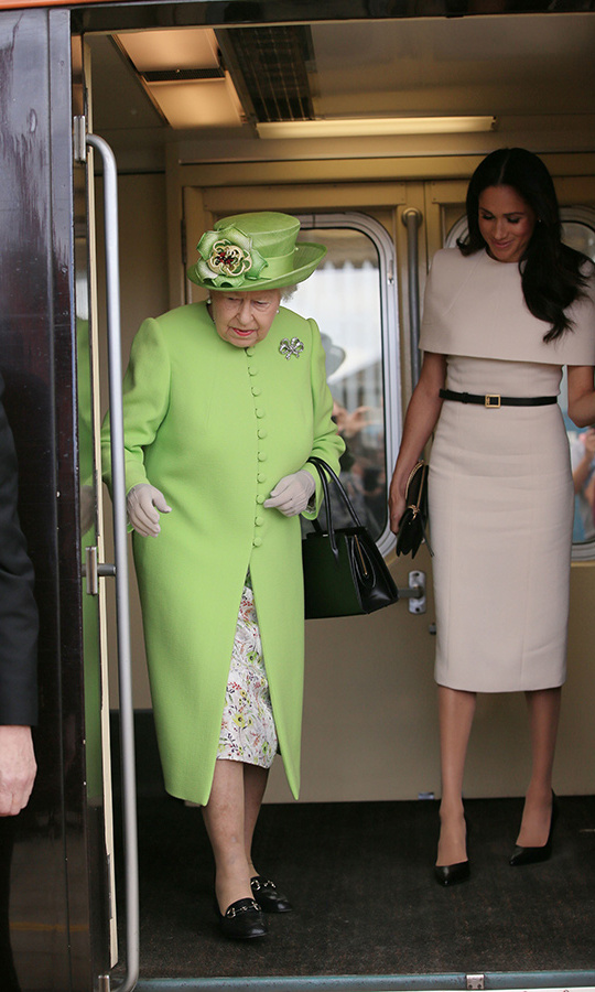 The monarch and her new granddaughter-in-law looked stunning as they arrived at Runcorn Station. The 92-year-old wore a lime-green skirt suit by Stewart Parvin - a subtle tribute to the Grenfell Tower victims on the first anniversary of the tragedy - along with a matching hat by Rachel Trevor Morgan and the Kensington Bow Broach. Meghan, 36, solidified the fact that her wedding gown designer Clare Waight Keller is now her official go-to, slipping into a stunning blush-hued Givenchy dress with caped detailing. She finished the look with a black belt and clutch by the designer and dark pumps. The piece de resistance? Pearl earrings gifted to her by the Queen. 