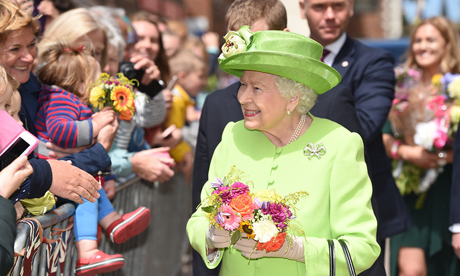 The Queen of walkabouts! After decades of greeting crowds, Meghan was sure to learn a thing or two from Her Majesty's expertise. Here, she holds two little bouquets while smiling and chatting with adorable children.