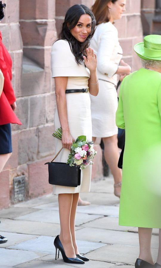 Meghan chose a subdued look for her first official joint engagement with the Queen, letting Her Majesty shine in a lime-green coat and matching hat. Turning to her go-to designer Clare Waight-Keller, the newest British Royal wore an off-white Givenchy caped dress with a black belt, purse and pumps.