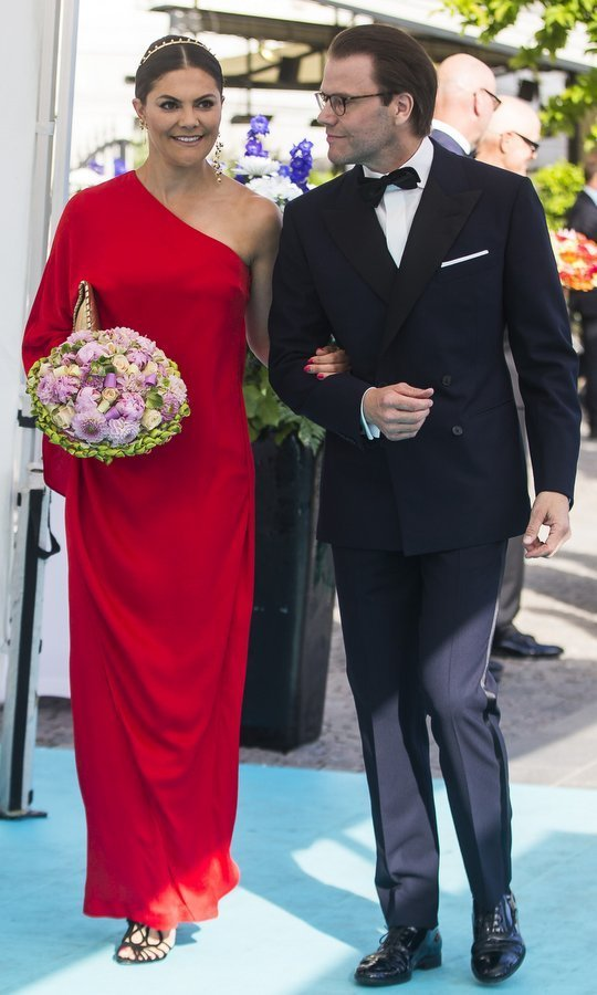 Crown Princess Victoria wore a bold red one-shouldered gown by Stylein along with a studded tiara for the 2018 Polar Music Prize ceremony, and arrived on the arm of her dashing husband Prince Daniel. 