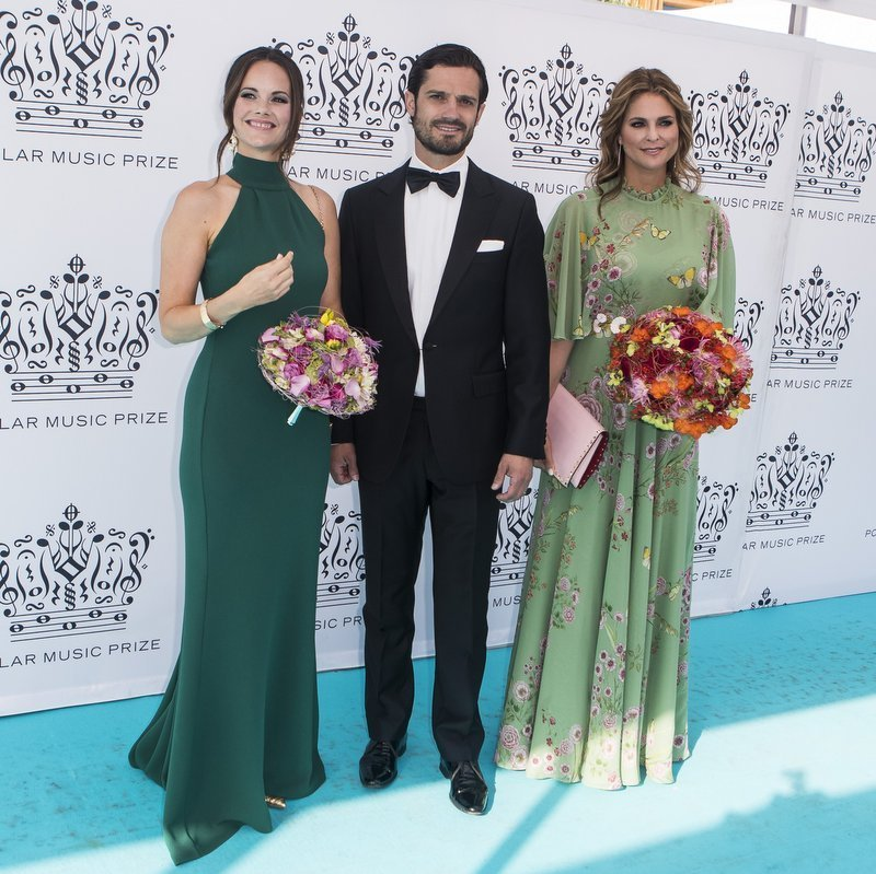 A week after Princess Adrienne's sweet christening, the Swedish royals pumped up the glam to attend the 2018 Polar Music Prize award ceremony at the Grand Hotel on June 14 in Stockholm. Prince Carl Philip of Sweden was handsome in a tuxedo accompanied by his wife Princess Sofia, left, in a forest green halter dress, and sister Princess Madeleine, wearing pale green floral Giambattista Valli with a pink clutch purse. 