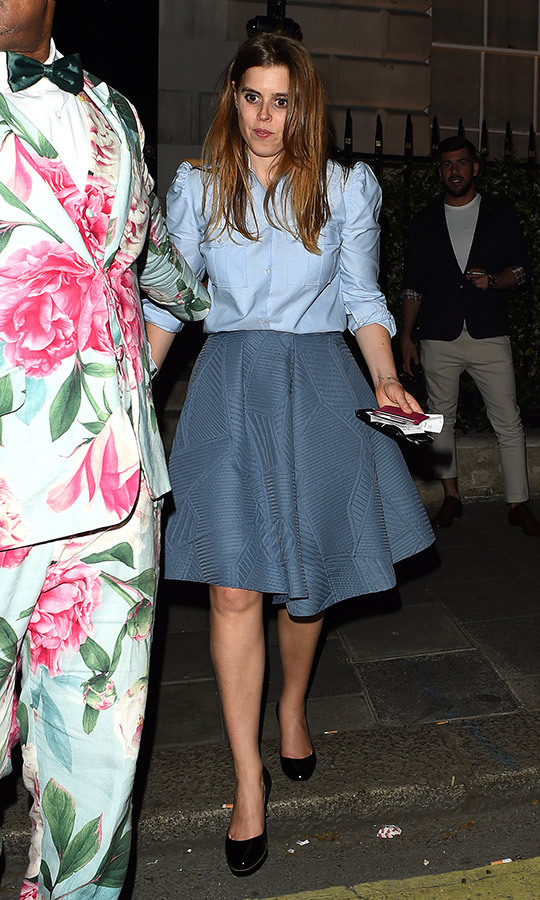 Princess Beatrice enjoyed a night out at Annabel's, where she turned heads in a stylish blue ensemble that featured a button-up shirt with embellished shoulders and a full, embossed skirt. She completed the look with black pumps.