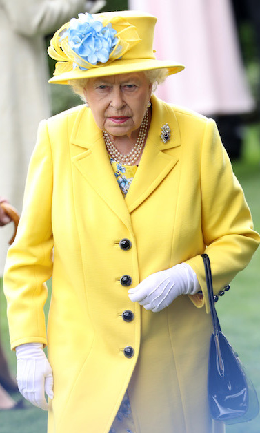 Queen Elizabeth II wore a beautiful floral dress underneath her bright yellow coat, pairing the look with a simple bag, white gloves and, of course, a matching hat.