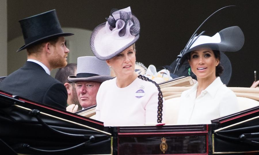 Meghan and Sophie rode side-by-side in the carriage en route to the Royal Ascot. The Countess of Wessex was pretty in pink, wearing a blush dress with black detailing down the sleeves and a black-and-white topper.