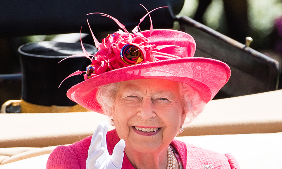 One of her most cherished events of the summer, the Queen couldn't hold back her smile as she waved to crowds on Ladies' Day. She was fittingly decked out in a pretty pink ensemble with a large floral embellishment on her hat.