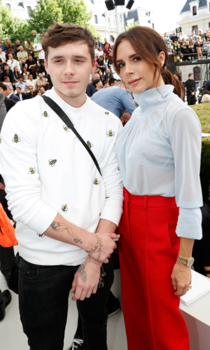 Mom and son date! Victoria and Brooklyn made for a fashionable pair at the show, with the mom-of-four rockin' a sheer pale blue top and red pants. Her son opted for a white sweater with bumble bees on it.