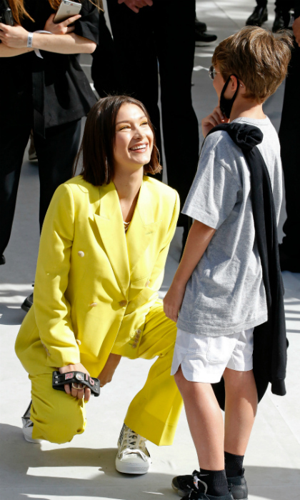 Bella Hadid was also in attendance at the Dior Paris show. The model wore an eye-catching highlighter yellow suit and couldn't stop showing off one of her accessories: a Dior phone case. At one point, she sweetly took a moment to talk with a young fan.