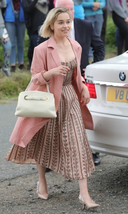 Emilia Clarke looked chic in a pale pink ensemble as she jaunted over to Rayne Church in Aberdeen, Scotland for her friends and co-stars Kit Harrington and Rose Leslie's wedding on June 23. 