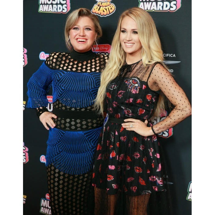 <em>American Idol</em> royalty Kelly Clarkson and Carrie Underwood caught up on the 2018 Radio Disney Music Awards carpet at Loews Hollywood Hotel on June 22. The reality show winners dazzled in patterned dresses at the event. 
