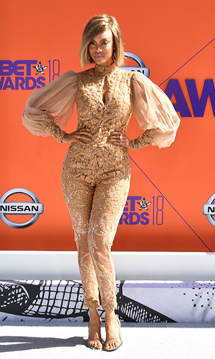 Tyra Banks was smizing as she struck a pose on the red carpet in a beige embroidered silk jumpsuit. 