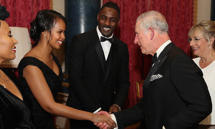 "A few months before they made their well-heeled appearance at Prince Harry and Meghan's royal wedding, actor Idris Elba and partner Sabrina Dhowre shook hands with Prince Charles. The trio was at Buckingham Palace in December 2018 for the One Million Young Lives dinner. Before the event, the star of <em>The Mountain Between Us</em> told <em>Sky News</em> that ""it's great"" to see Meghan Markle joining the royal fold because ""of course our society is one of mixed heritage."" He continued that regardless of her colour, ""as a strong woman marrying into our royal family, she's going to be a role model for any woman.""