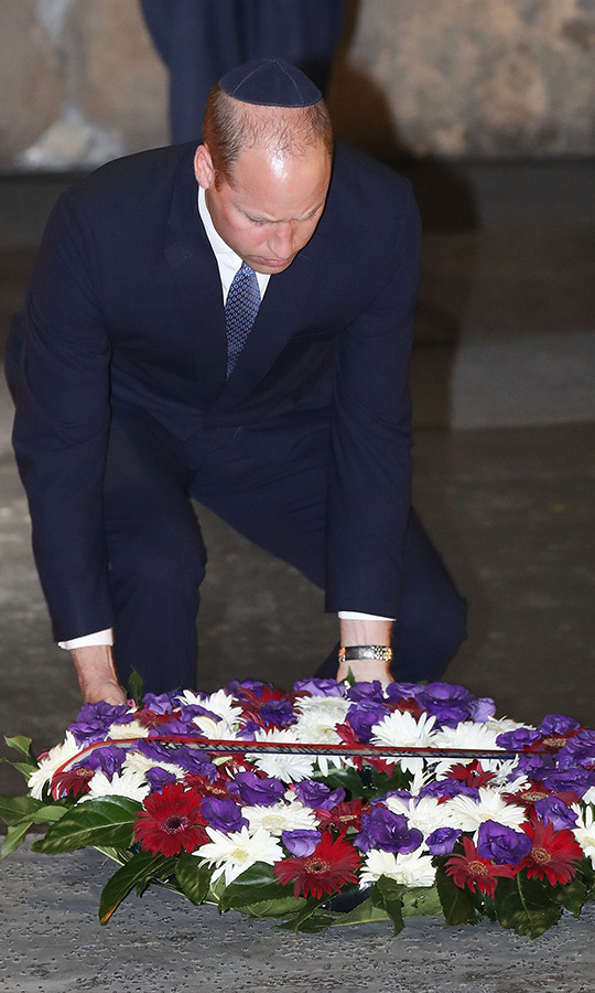 "Prince William laid a wreath of red, white and purple flowers in Yad Vashem's Hall of Remembrance. He wore a traditional skull cap, or ""kippah,"" during his visit. 