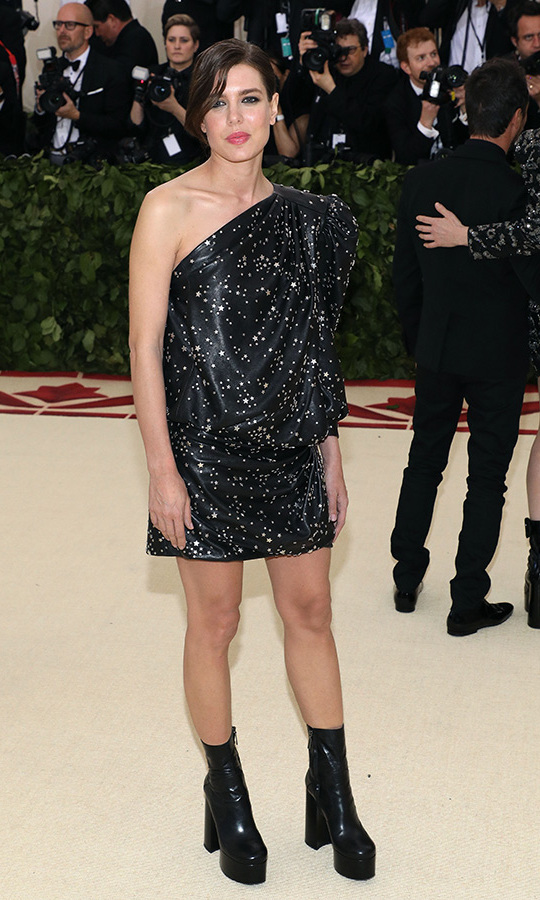 Joining a gaggle of high-profile models and actresses dressed by Saint Laurent at the 2018 Met Gala, Prince Albert's niece was a vision in a starry one-shoulder black mini dress, which she paired with sky-high platform boots. Keeping the rest of her look typically pared down, the royal shirked jewellery and wore her hair in a loose updo and a pink lip.