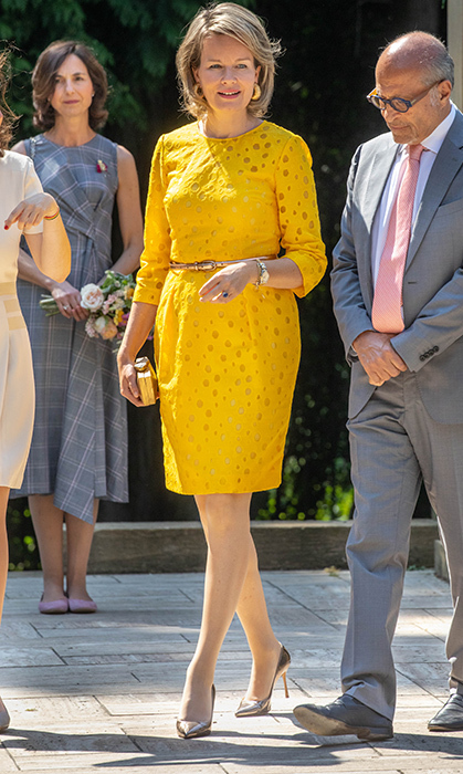 Queen Mathilde showed off her sunny disposition in a bright yellow summer dress during a meeting at the Art Deco Exhibition Melancholia on July 4 in Brussels. She paired the look with metallic heels and a simple clutch.