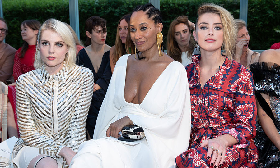 Tracee Ellis Ross was throwing out goddess vibes in a plunging white dress and oversized gold earrings at the Valentino show, where she sat sandwiched between blondes Lucy Boynton and Amber Heard.
