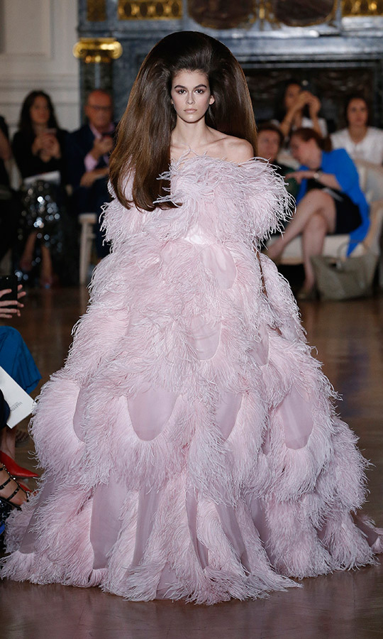 Kaia Gerber's hair soared to new heights at the Valentino couture show as she strutted the runway in a spectacular feathered frock.