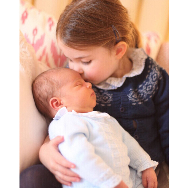 Princess Charlotte gave her new little brother Prince Louis a smooch in one of the first official portraits celebrating Prince William and Kate's third child. The shot, which was taken by their proud mom, also marked the adorable big sister's third birthday.