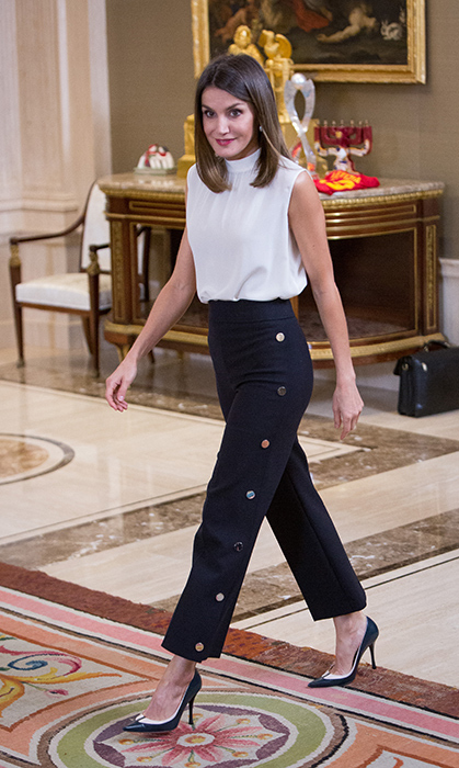 Queen Letizia showed off her classic sense of style for a meeting with the Spanish U-17 women's soccer team at Zarzuela Palace on July 5. She dazzled in a pair of recycled Hugo Boss 'Telareama' Snap Detail Wide-Leg Pants, white and black pumps and a high-neck blouse for the occasion.