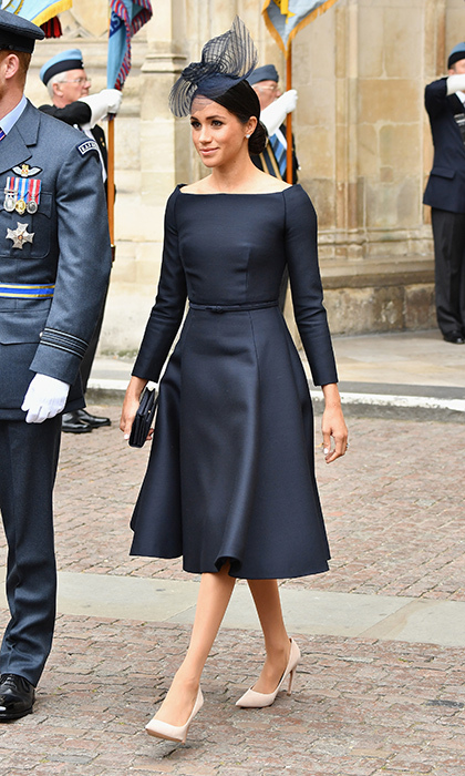 Meghan wore a designer that's new to her wardrobe: Dior! The custom dress featured her favourite elements of late - a very thin belt at the waist and bateau neckline. She changed it up, however, with a fuller skirt, and paired the dark ensemble with a light pair of suede pumps. Topping it off was a Stephen Jones fascinator.