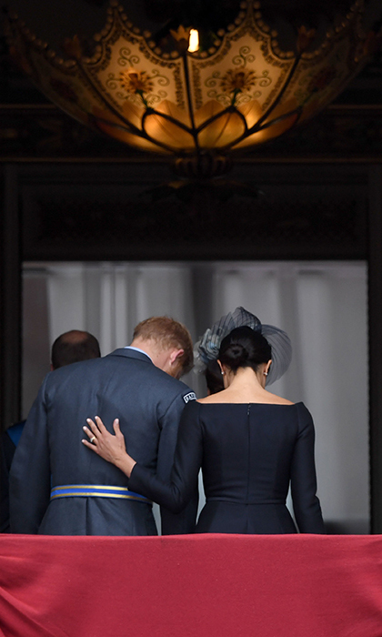 Awww! Meghan shared a sweet moment with her husband, placing a delicate hand on his back, as they left the balcony following the flypast.
