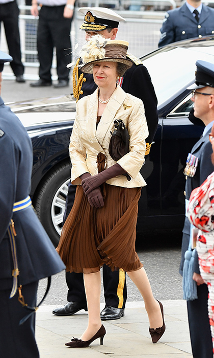 The Queen's daughter, Princess Anne, looked festive in a feathery oversized hat, pleated brown skirt, cream jacket and long gloves. 
