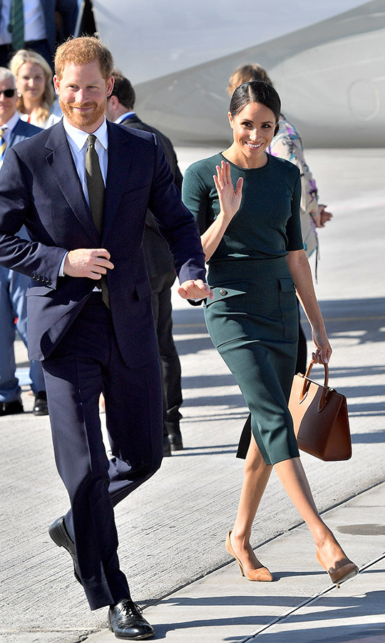 "The Duchess of Sussex made her first overseas trip as an official royal alongside her husband Prince Harry. While arriving at the Dublin Airport on July 10, 2018, Meghan paid homage to her the Emerald Isle in a deep-green Givenchy blouse and matching 'Patch Pocket' skirt, paired with brown suede pumps, the tan Strathberry Midi Tote handbag and a low chignon. She also wore Vanessa Tugenhaft's ""Precious"" earrings - little clover studs embellished with diamonds!