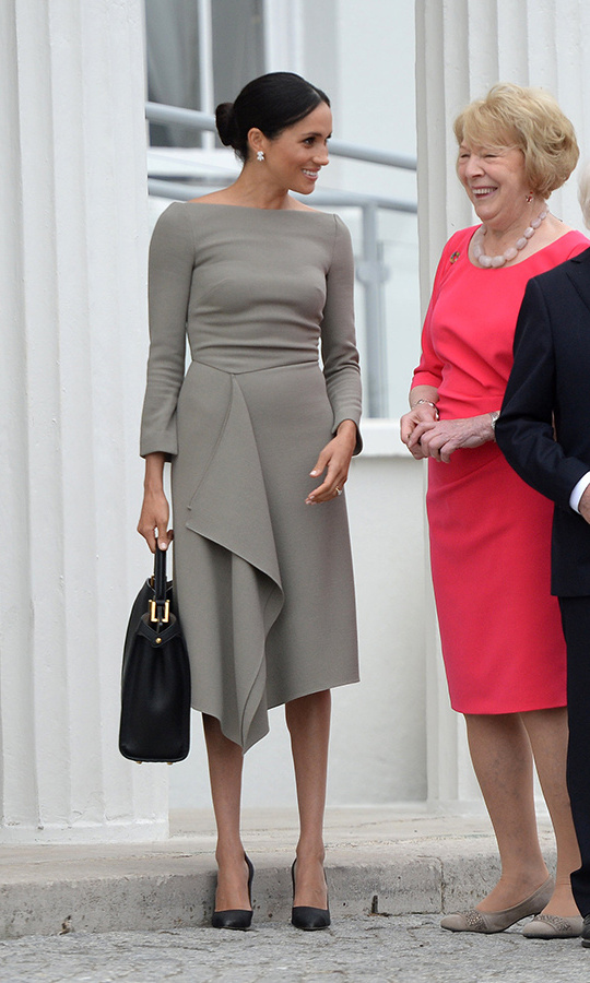 Meghan kicked off the second day of her two-day visit to Ireland with Prince Harry in a stunning grey dress by her good friend Roland Mouret, which she wore to meet President Michael D. Higgins at Aras an Uachtarain. She carried a large black Fendi tote and completed the look with black Paul Andrew pumps and a dazzling pair of Birks Snowflake Snowstorm Diamond earrings. The 36-year-old wore her sleek brown locks in a chic updo and her makeup looked typically flawless – subtle foundation and eye makeup accentuated her pretty features.  
