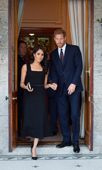 While leaving Glencairn, the residence of British Ambassador Robin Barnett, the duke held onto Meghan's hand to help her through the doorway.