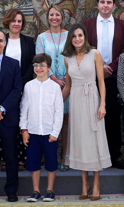 While welcoming an audience at the palace, Letizia opted for a summery beige wrap dress and brown suede slingback heels.