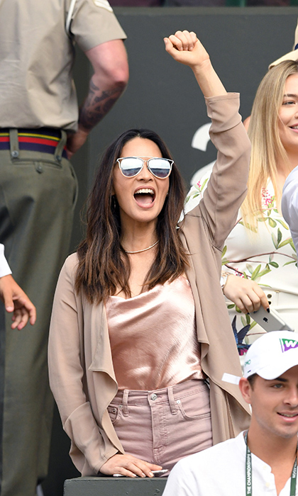 Olivia Munn was brimming with excitement on day ten of Wimbledon as the huge tennis fan took her seat in the stands - though she was standing quite a bit! The <em>X-Men</em> star wore a pretty pink camisole with matching cut-off shorts and a silky nude robe, which she paired with mirrored shades.