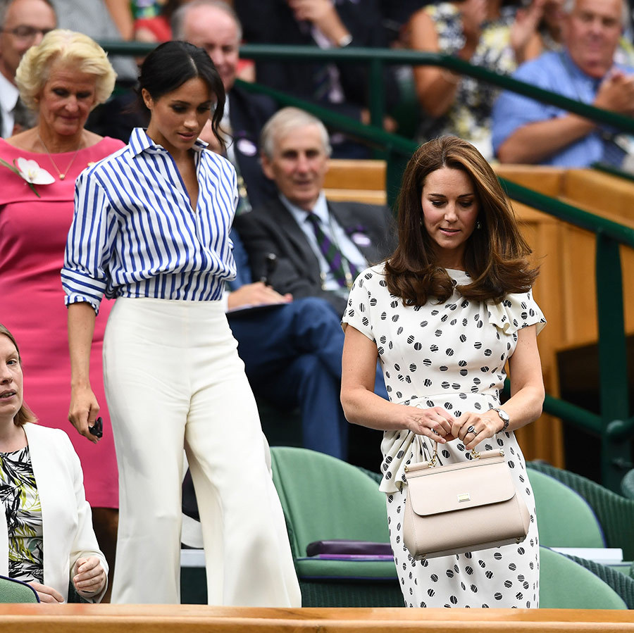 Meghan wore a striped Ralph Lauren shirt with wide-leg cream pants and a messy bun.