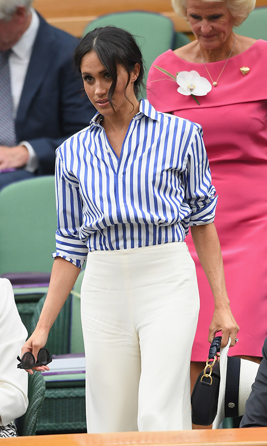 Meghan brought back her messy bun to watch bestie Serena Williams compete in the women's finals. She wore a Ralph Lauren ensemble - a crisp striped shirt and wide-legged cream pants - and carried a handbag by Altuzzara, Illesteva sunnies and a Maison Michel Panama hat.